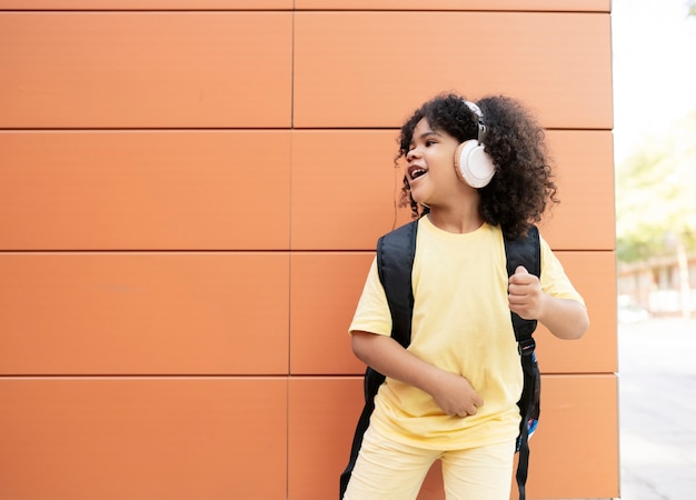 Little afro boy stands on an orange background listening to music with headphones very happy