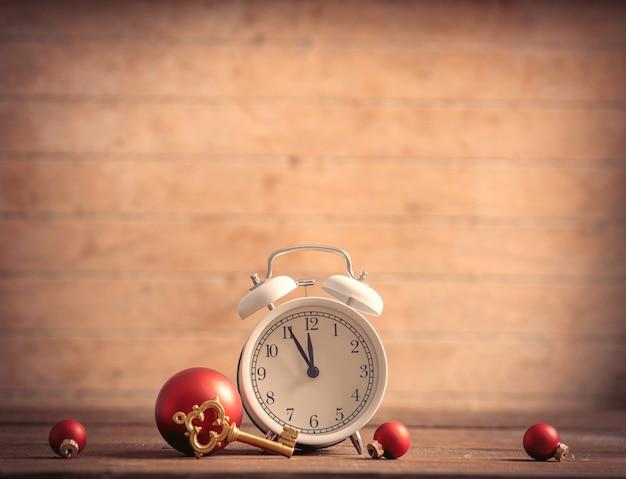 木製のテーブルに小さな目覚まし時計と鍵