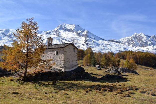 유럽 국립 공원에서 눈 덮인 산 배경으로 바위에 작은 고산 예배당 건물