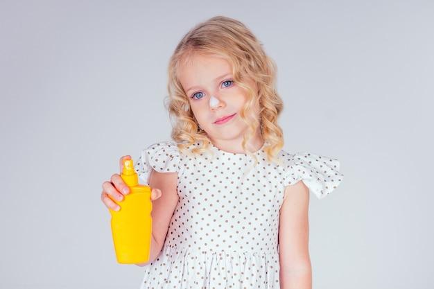 手にボトルの日焼け止めを保持しているかわいいドレスを着た小さくて美しい金髪の巻き毛の髪型の女の子。青い目、完璧な肌、鼻のしみのspfクリームのクローズアップスタジオの白い背景の上の肖像画