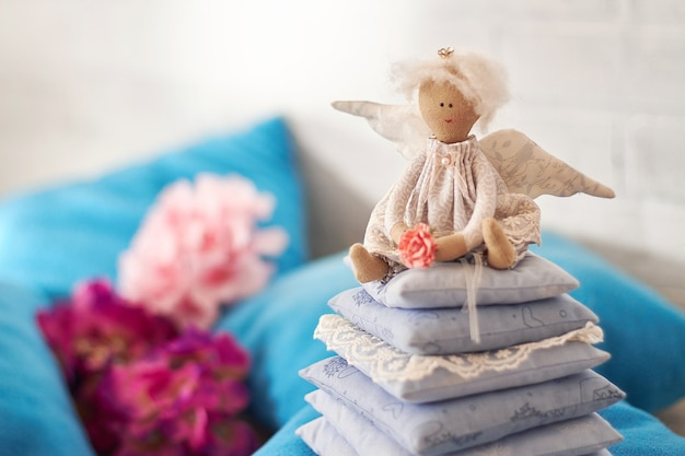 Little angel doll sitting on a pillow. valentine's day. children's toy hand made