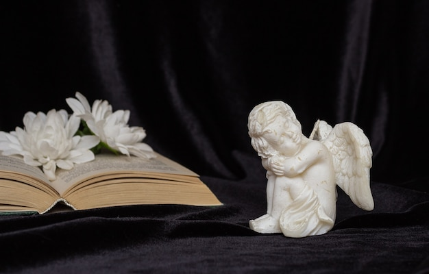 Little angel with wings on a black background, flowers and a book, free space for text