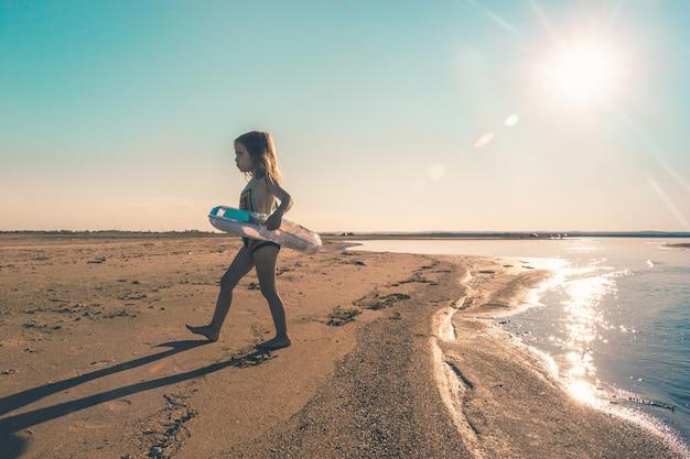Маленькая злая девочка покидает море, не хочет плавать в холодной воде. скопируйте пространство. тонированное фото.