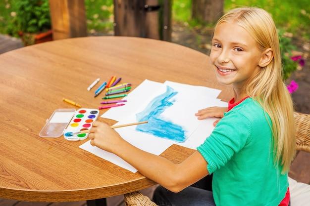 Маленький художник за работой. вид сверху милая маленькая девочка, которая что-то рисует на бумаге и улыбается, сидя за столом и на открытом воздухе