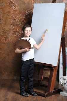 The little artist boy painting on canvas