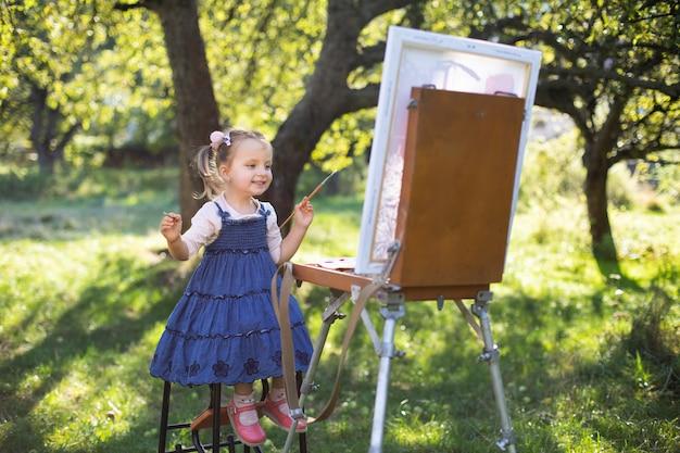 Маленький художник. мольберт и живопись на холсте. маленький ребенок, милая 3-летняя девочка в джинсовом платье, рисует с мольберта на лужайке в зеленом солнечном летнем саду или парке.