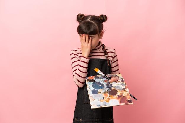 疲れて病気の表情でピンクの壁に分離されたパレットを保持している小さなアーティストの女の子