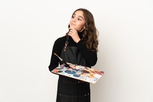 Маленькая девочка художника держит палитру на белом фоне и смотрит вверх