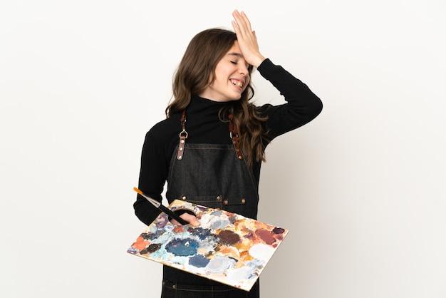 白い背景で隔離のパレットを保持している小さなアーティストの女の子は、何かを実現し、解決策を意図しています