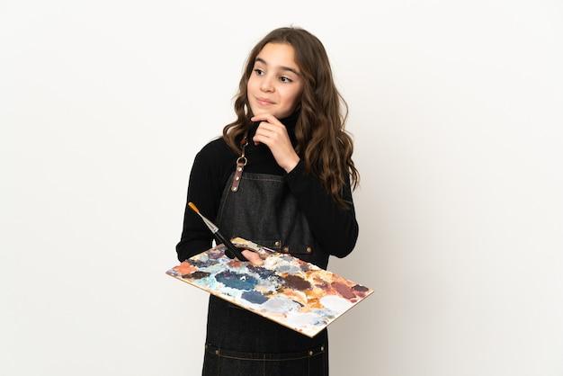 横を見て笑っている白い背景で隔離のパレットを保持している小さなアーティストの女の子