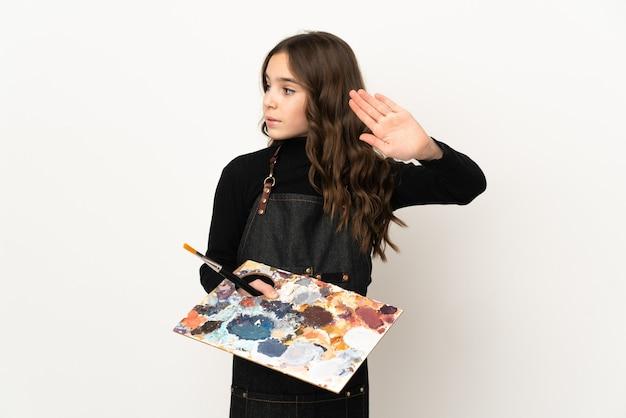 Маленькая девочка-художник, держащая палитру, изолированную на белом фоне, делает стоп-жест и разочарована