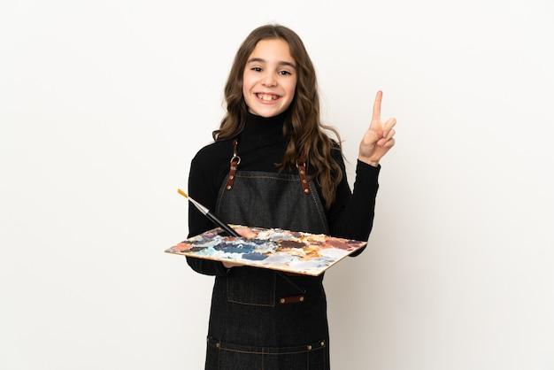 Маленькая девочка-художник держит палитру на белом фоне, указывая на отличную идею