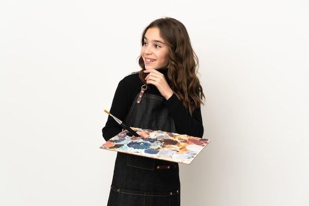 Маленькая девочка художника держит палитру, изолированную на белой стене, глядя вверх, улыбаясь