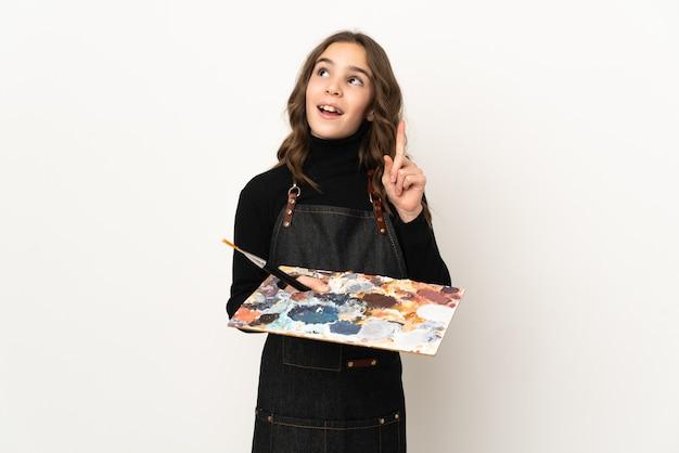 Маленькая девочка художника держит палитру, изолированную на белой стене, думая об идее, указывая пальцем вверх