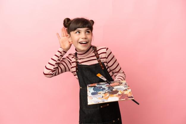 分離されたパレットを保持している小さな芸術家の女の子 Premium写真