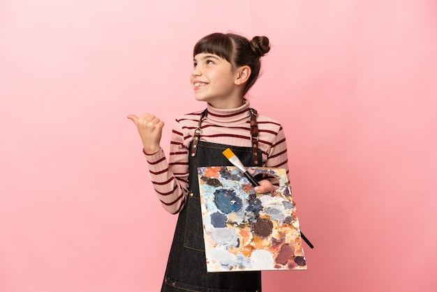 分離されたパレットを保持している小さな芸術家の女の子
