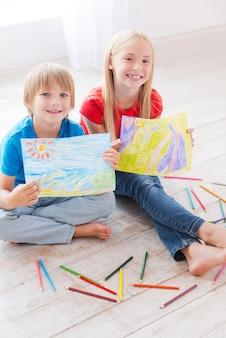 Маленькие художники. двое симпатичных маленьких детей показывают картинки, которые они рисуют, сидя на деревянном полу