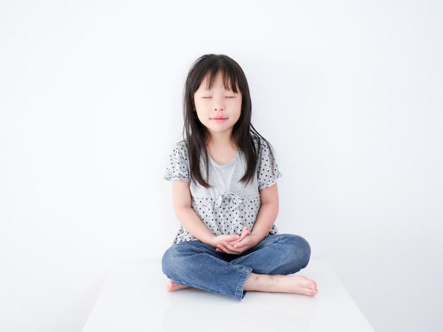 Little asain girl meditation over white background.
