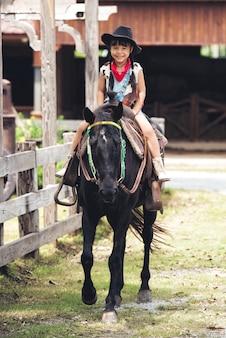 모자와 작은 아시아 어린이 소녀 행복한 미소는 검은 말을 타고있다