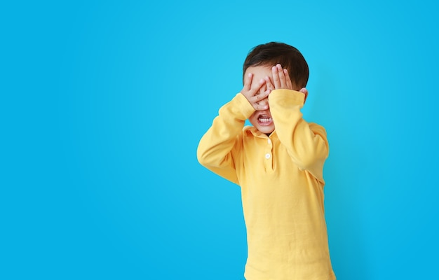 Little asian baby boy covering eyes with hands isolated on blue