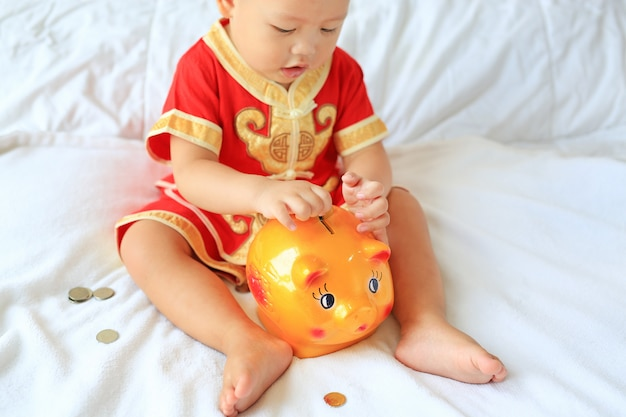 Little asian baby boy in traditional chinese dress putting some coins into a piggy bank on bed.