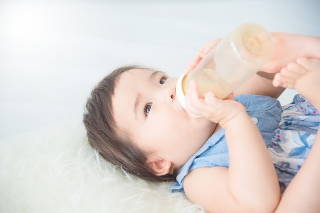 Little asian baby girl drinking milk from bottle by herself on bed