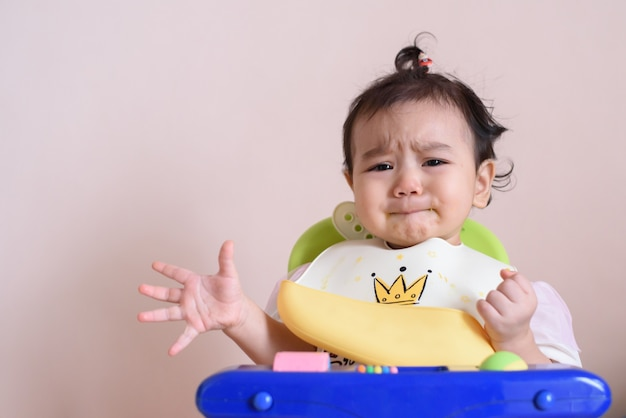 Little asian baby girl unhappy face in dining time, sadness, baby expression concept