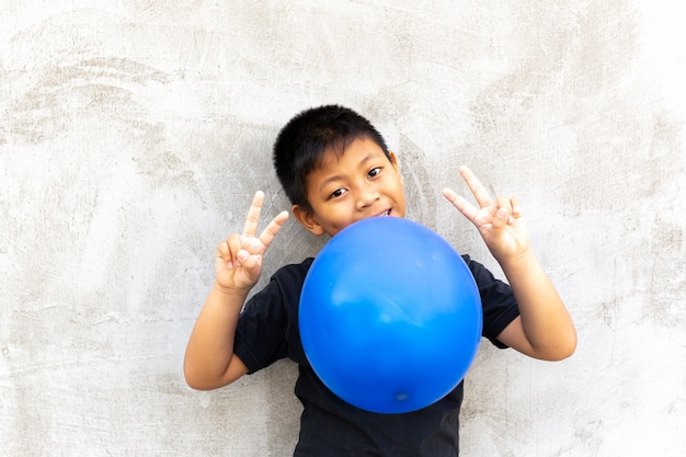Little asian boy biting balloon with finger up on grey background.
