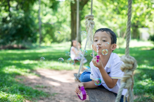A little asian boy blowing bubbles, playing with joy and happiness in the beautiful and green nature.