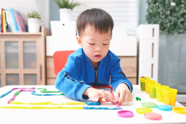 Little asian boy child having fun playing colorful modeling clay / play dough at home, child at home, kindergarten closed