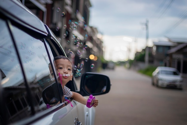 A little asian boy happily blows bubbles out of a car window.