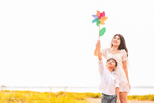 Little asian boy and his mom playing colorful rainbow turbine in meadow.