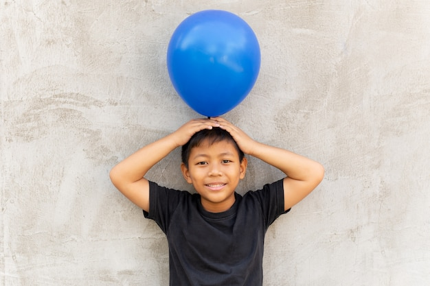 Little asian boy holding balloon on top of his head with grey background.