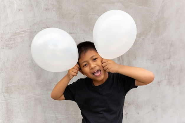 Little asian boy holding white balloons over grey concrete background.