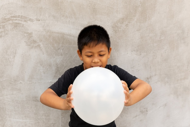 Little asian boy pressing white balloons over grey concrete background.