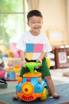 Little asian boy riding bicycle toy inthe house with happy face