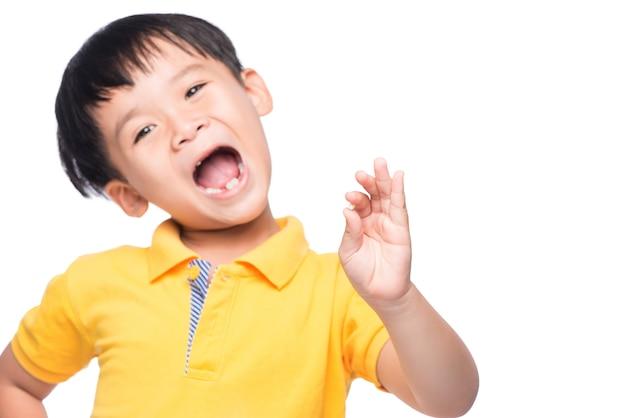 彼の失われた牛乳の歯を手に見せている小さなアジアの少年-クローズアップ