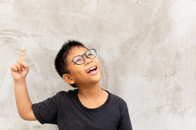 Little asian boy smiling with finger pointing upward.