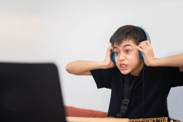 Маленький азиатский мальчик учится музыке саксофонного инструмента онлайн дома