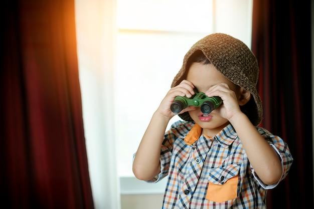Little asian boy with toy sailing boat in hotel room. travel and adventure concept