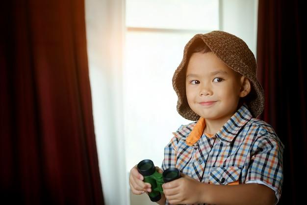 ホテルの部屋のおもちゃのセーリングボートと小さなアジアの少年。旅行と冒険のコンセプト