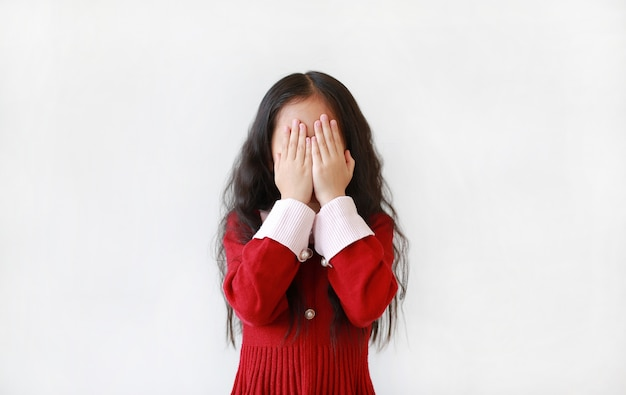 Little asian child girl covering eyes with hands isolated .