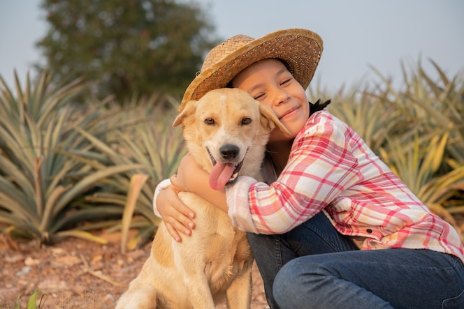 Little asian child girl and dog. happy cute girl in jeans overall and hat playing with dog in pineapple farm, summertime in countryside, childhood and dreams, outdoor lifestyle.