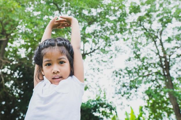 Little asian child girl doing yoga in the public park.