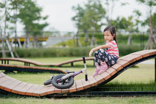Little asian child girl fallen from bike at playground