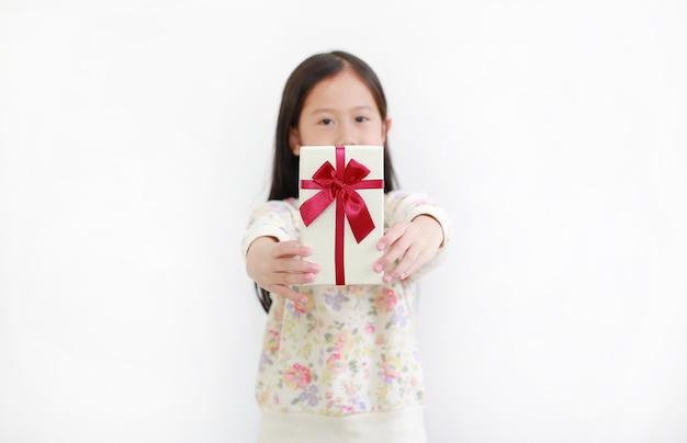 小さなアジアの子供の女の子はあなたにギフトボックスを与えます