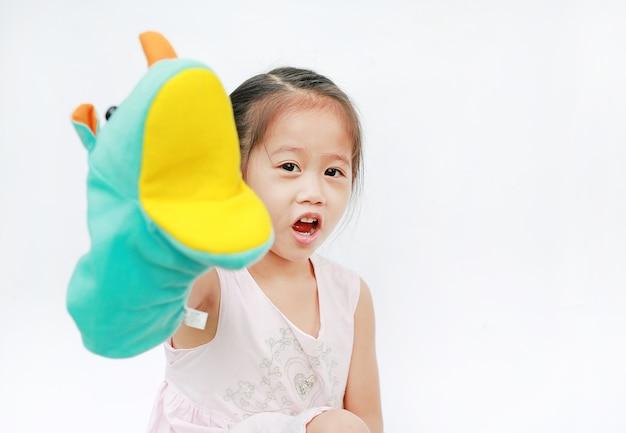 작은 아시아 아이 소녀 손 착용 하 고 흰색 배경에 코뿔소 인형 연주.