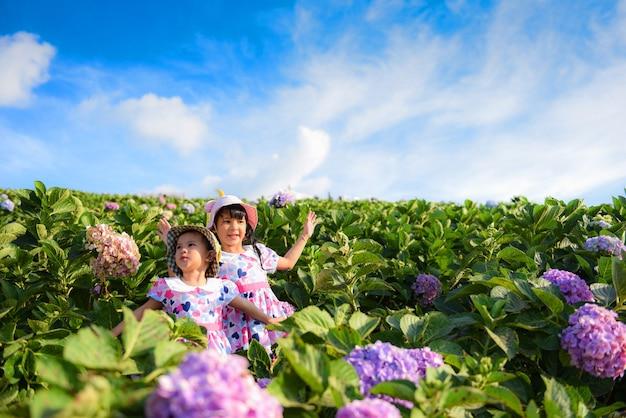 小さなアジアの子供の女の子は庭の花の外で遊ぶ幸せな笑顔の子供たちと楽しんでいます