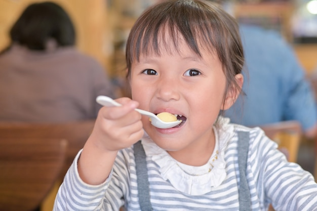 Little asian child girl having lunch on table in restaurant