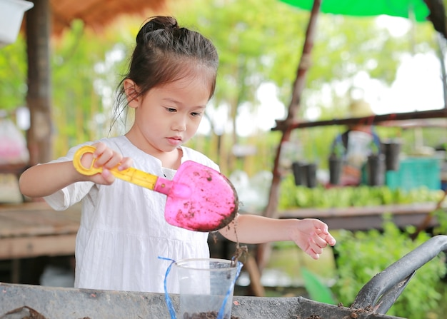 Little asian child girl planting the tree in pot.